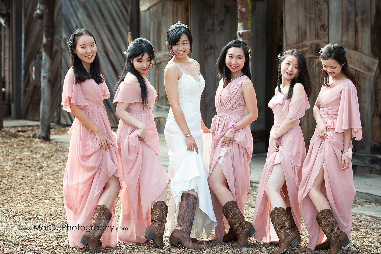 bride in white dress and bridesmaids in pink dresses showing cowboy boots at Long Branch Saloon & Farms in Half Moon Bay