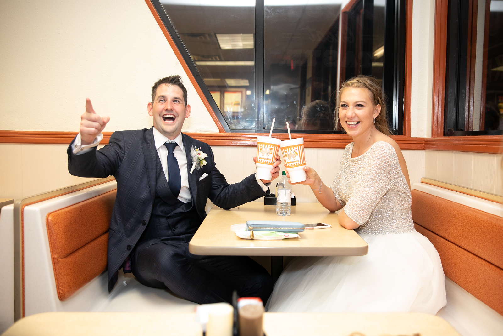 newlywed couple smiling at a fastfood restaurant as they cheers their styrofoam cups