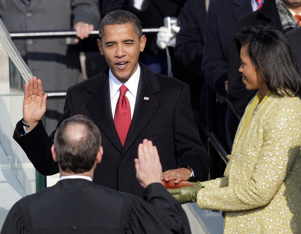 . Barack Obama, left, joined by his wife Michelle, takes the oath of office from Chief Justice John Roberts to become the 44th president of the United States at the U.S. Capitol in Washington, Tuesday, Jan. 20, 2009.  (AP Photo/Jae C. Hong)