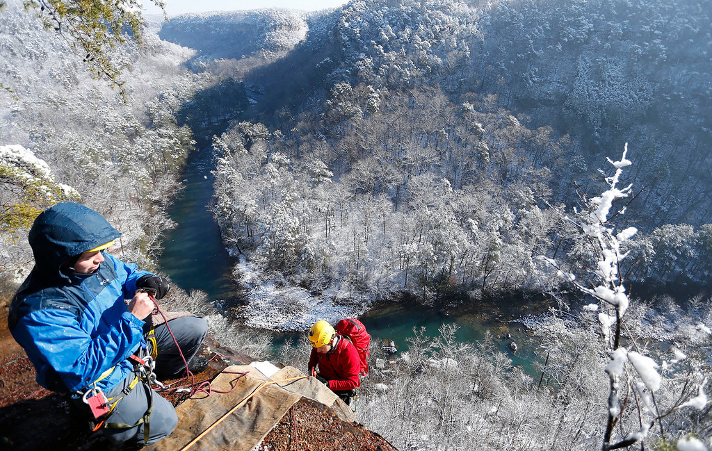 . Hobie McQuade, left,  assists Israel Partridge of True Adventure Sports prepare as he prepares to rappel into a snow and ice covered Little River Canyon Thursday, Feb. 13,  2014 near Fort Payne Ala.  A winter storm that dropped as much as a foot of snow on parts of north Alabama over two days left almost 25,000 homes and businesses without electricity Thursday and snarled traffic. (AP Photo/Hal Yeager)
