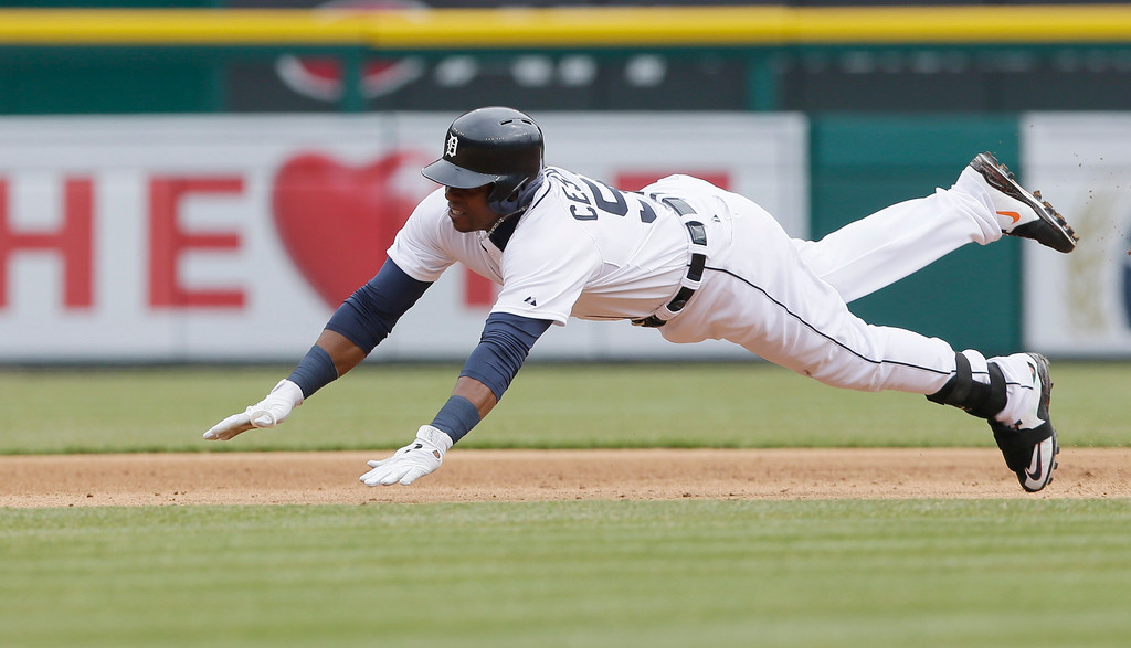 . Detroit Tigers\' Yoenis Cespedes slides into third base with a triple during the sixth inning of an opening day baseball game against the Minnesota Twins in Detroit, Monday, April 6, 2015. (AP Photo/Carlos Osorio)