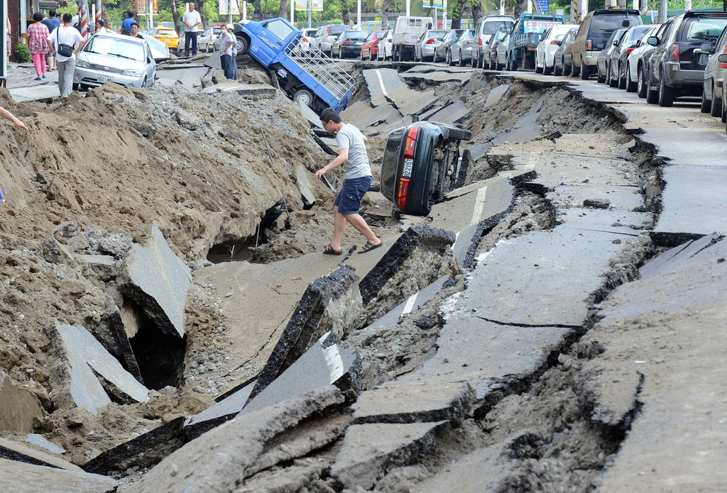 . A local resident crosses the explosion site in southern Kaohsiung city on August 1, 2014.  A series of powerful gas blasts killed at least 22 people and injured up to 270 in the southern Taiwanese city of Kaohsiung, overturning cars and ripping open roads, officials said.   AFP PHOTO / SAM  YEH/AFP/Getty Images