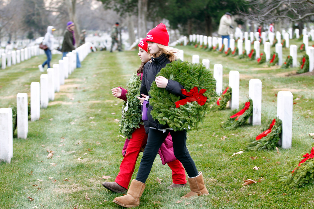 . Volunteers help to lay holiday wreaths at graves at Arlington National Cemetery in Arlington, Va., Saturday Dec. 15, 2012, during Wreaths Across America Day. Wreaths Across America was started in 1992 at Arlington National Cemetery by Maine businessman Morrill Worcester and has expanded to hundreds of veterans\' cemeteries and other locations in all 50 states and beyond. (AP Photo/Jose Luis Magana)