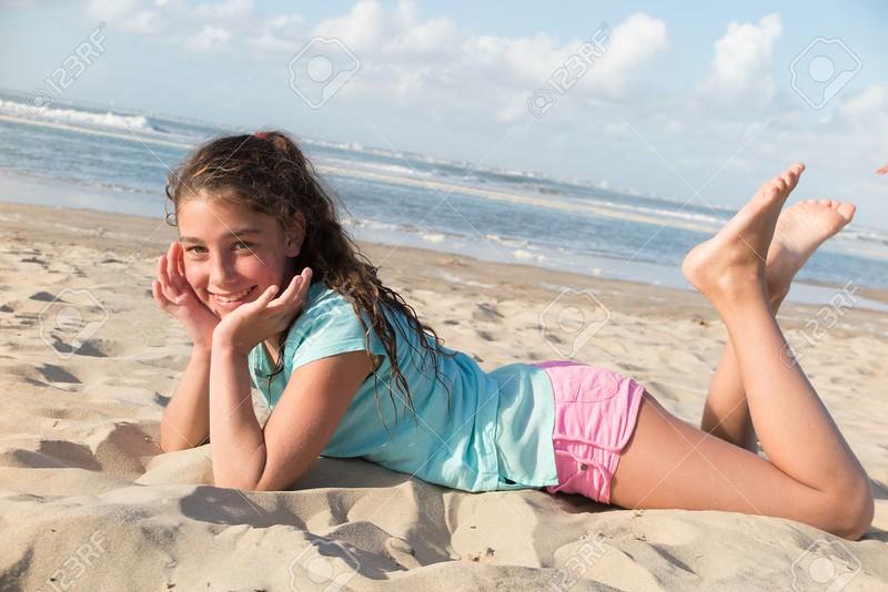 Happy girl enjoying sunny day at beach, lying on beach