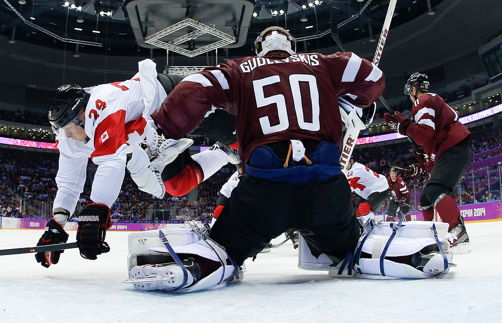 . Canada forward Corey Perry trips over Latvia goaltender Kristers Gudlevskis in the first period of a men\'s ice hockey game at the 2014 Winter Olympics, Wednesday, Feb. 19, 2014, in Sochi, Russia. (AP Photo/Julio Cortez, Pool)
