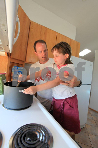 Father shows his daughter the art of cooking.