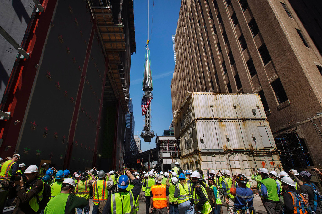 . Members of the media and workers at the Ground Zero site take photographs as the final piece of a spire is lifted to the top of One World Trade Center, in New York May 2, 2013. The piece will be attached at a later date. REUTERS/Lucas Jackson