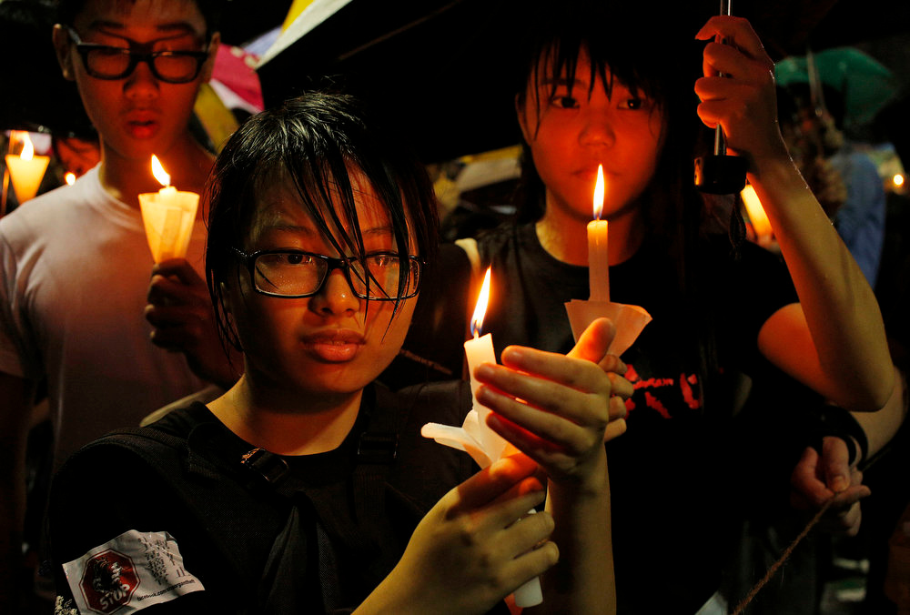 . Students hold candles in heavy rain as tens of thousands of people attend a candlelight vigil at Hong Kong\'s Victoria Park Tuesday, June 4, 2013 to mark the 24th anniversary of the June 4th Chinese military crackdown on the pro-democracy movement in Beijing. (AP Photo/Vincent Yu)