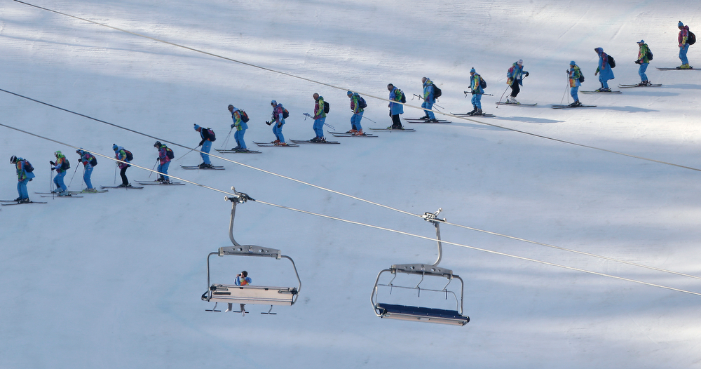 . Workers groom a course at the Rosa Khutor alpine center  after the women\'s super-G competition at the 2014 Winter Olympics, Saturday, Feb. 15, 2014, in Krasnaya Polyana, Russia. (AP Photo/Charlie Riedel)