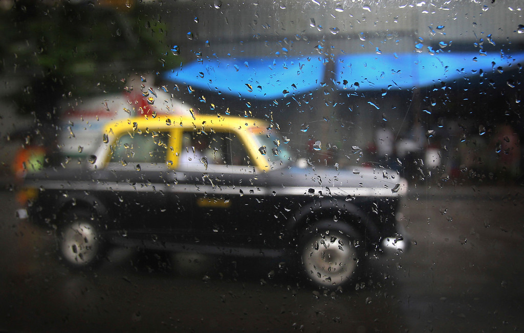 . In this Tuesday, July 30, 2013, a Mumbaiís Premier Padmini taxi is seen as rain droplets gather on the window of another taxi in Mumbai, India. More than 4500 Premier Padmini taxis are expected to be banned from the roads in Mumbai this year, starting in August,  in line with a government order that bans cabs that are more than 20 years old. (AP Photo/Rafiq Maqbool)