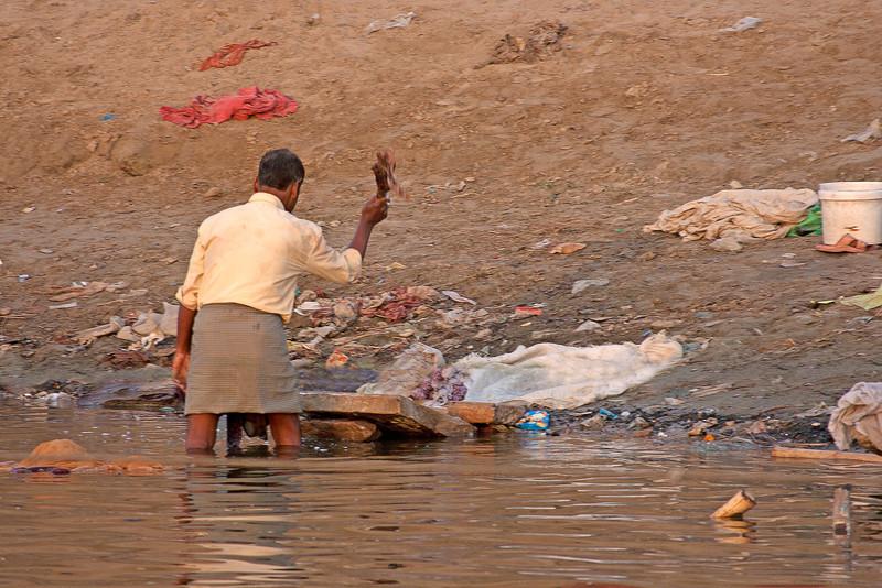 men washing laundry on the bank of the Ganges, India