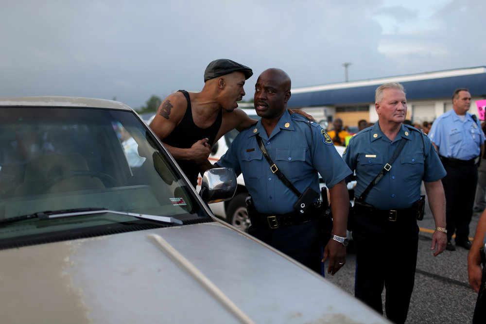 . Demonstrator Artez Hurston (L) speaks to Capt. Ronald Johnson of the Missouri State Highway Patrol, who was appointed by the governor to take control of security operations in the city of Ferguson after the shooting death of Michael Brown, on August 17, 2014 in Ferguson, Missouri. Violent outbreaks have taken place in Ferguson since the shooting death of Michael Brown by a Ferguson police officer on August 9th.  (Photo by Joe Raedle/Getty Images)