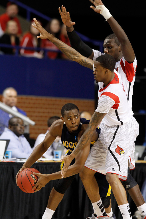 . North Carolina A&T guard Lamont Middleton (30) is covered by Louisville guard Kevin Ware (5) and center Gorgui Dieng (10) during the first half of their second-round NCAA college basketball tournament game, Thursday, March 21, 2013, in Lexington, Ky. (AP Photo/James Crisp)