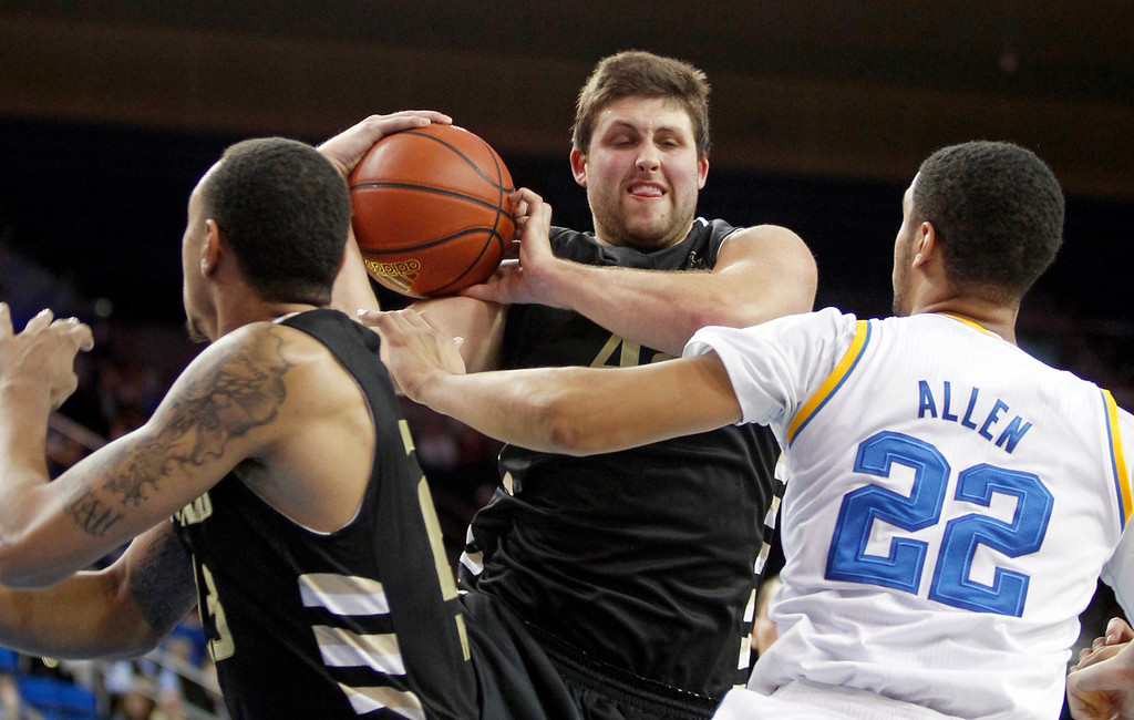 . Oakland center Corey Petros, center, pulls down a rebound between teammate Tommie McCune, left, and UCLA guard Noah Allen (22) in the second half of an NCAA college basketball game Tuesday, Nov. 12, 2013, in Los Angeles. UCLA won 91-60.  (AP Photo/Alex Gallardo)