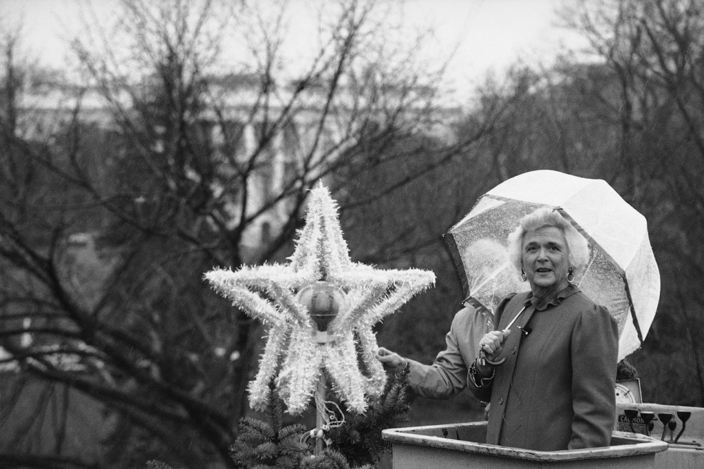 . Barbara Bush, wife of Vice-President George Bush, asks photographers if they are through taking pictures, as she stands suspended in a bucket truck in the rain, while putting the star atop the National Christmas Tree Dec.1, 1981 in Washington. (AP Photo/Jeff Taylor)