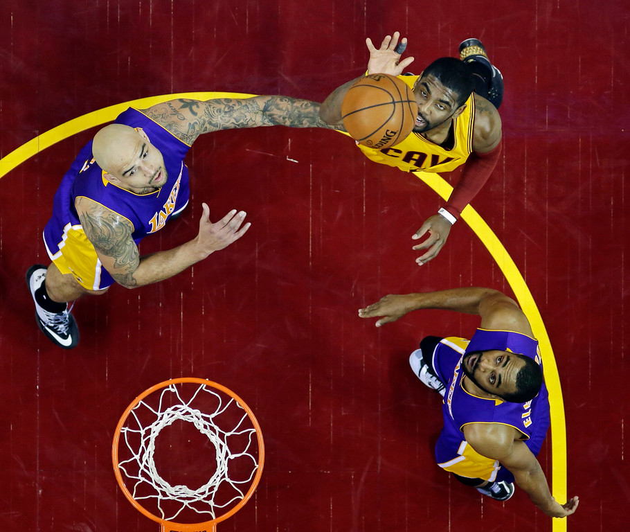 . Cleveland Cavaliers\' Kyrie Irving lofts a shoot against Los Angeles Lakers\' Robert Sacre, left, and Wayne Ellington in an NBA basketball game Sunday, Feb. 8, 2015, in Cleveland. (AP Photo/Mark Duncan)