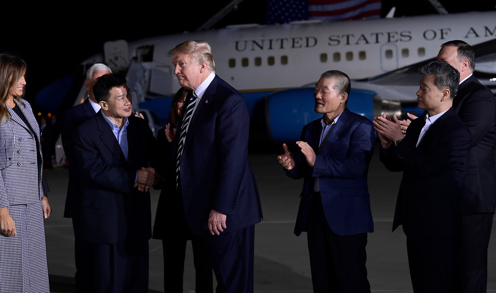 . President Donald Trump, center left, shakes hands with Tony Kim, with Kim Dong Chul, third right, and Kim Hak Song, second right, three Americans detained in North Korea for over a year, after they arrived at Andrews Air Force Base in Md., Thursday, May 10, 2018. First lady Melania Trump watches at left. (AP Photo/Susan Walsh)