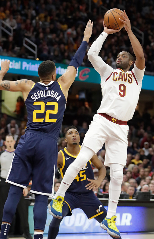 . Cleveland Cavaliers\' Dwyane Wade (9) shoots over Utah Jazz\'s Thabo Sefolosha (22), from Switzerland, in the second half of an NBA basketball game, Saturday, Dec. 16, 2017, in Cleveland. (AP Photo/Tony Dejak)