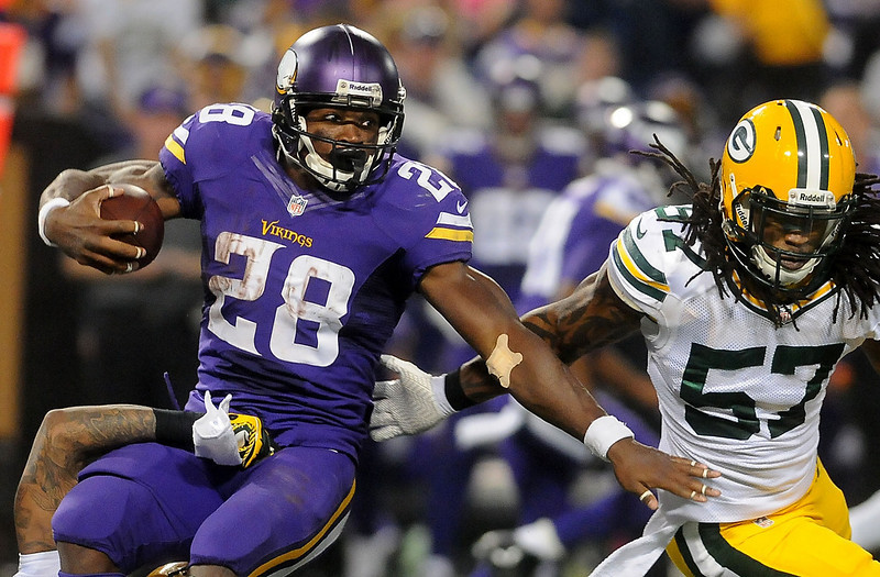 . Minnesota Vikings running back Adrian Peterson gains a few yards before he  is stopped by Green Bay Packers strong safety Morgan Burnett during the third quarter. (Pioneer Press: Sherri LaRose-Chiglo)