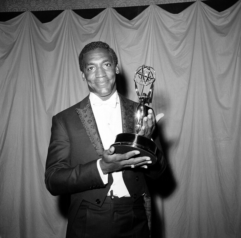 """. Actor and comedian Bill Cosby poses with his Emmy statuette at the annual Primetime Emmy Awards in New York City, May 22, 1966.  The 28-year-old won for his role in \""""I Spy\"""" and became the first black actor to win an Emmy for a leading role in a television series.  (AP Photo)"""