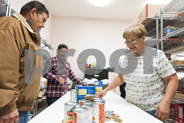 11/21/17 Wesley Bunnell | Staff The New Britain Salvation Army has seen a 100 percent increase in families looking for assistance from the food pantry since August in part due to the hurricanes. Food pantry volunteers Harry Cabaralo, L, Wilson Correa and Mirta Soto organize food items on a table to be distributed.
