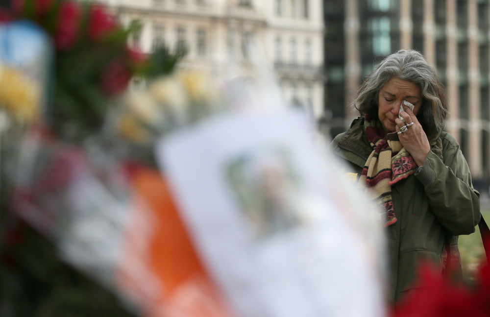 . Joanna Vignola from London reacts as she lays flowers at the foot of the Nelson Mandela statue in Parliament Square in London, Friday, Dec. 6, 2013.  Mandela passed away Thursday night after a long illness. He was 95. As word of Mandela\'s death spread, current and former presidents, athletes and entertainers, and people around the world spoke about the life and legacy of the former South African leader. (AP Photo/Alastair Grant)