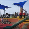 green plastic slide on embankment and moulded clambering boulders and rubber softfall and spinner and parallel slide bars and blue shade structures
