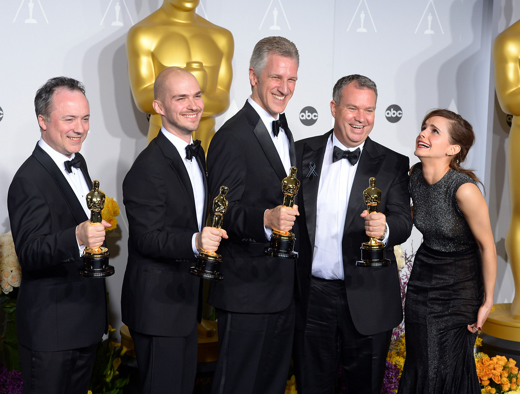 ". Tim Webber, Chris Lawrence, David Shirk, and Neil Corbould accept the Oscar for ""Achievement in Visual Effects\"" for the movie Gravity, with Emma Watson backstage at the 86th Academy Awards at the Dolby Theatre in Hollywood, California on Sunday March 2, 2014 (Photo by David Crane / Los Angeles Daily News)"