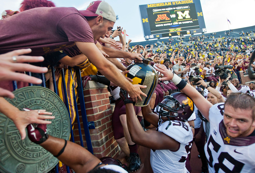 . Minnesota fans celebrate with players as defensive lineman Michael Amaefula (98) lifts the Little Brown Jug trophy after an NCAA college football game against Michigan in Ann Arbor, Mich., Saturday, Sept. 27, 2014. Minnesota won 30-14. (AP Photo/Tony Ding)