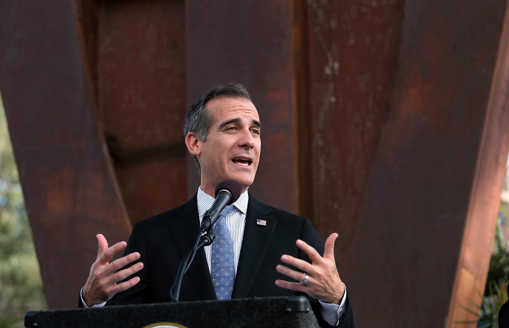 . Los Angeles Mayor Eric Garcetti speaks during a ceremony marking the 17th anniversary of the Sept. 11, 2001 terrorist attacks on the United States, at the Los Angeles Fire Department\'s training center Tuesday, Sept. 11, 2018. In the background is the largest fragment of the World Trade Center outside New York. (AP Photo/Reed Saxon)