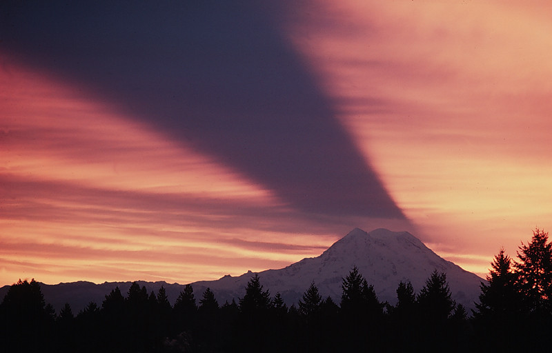 An inverted shadow of Mt. Rainier is projected on the clouds at sunrise.