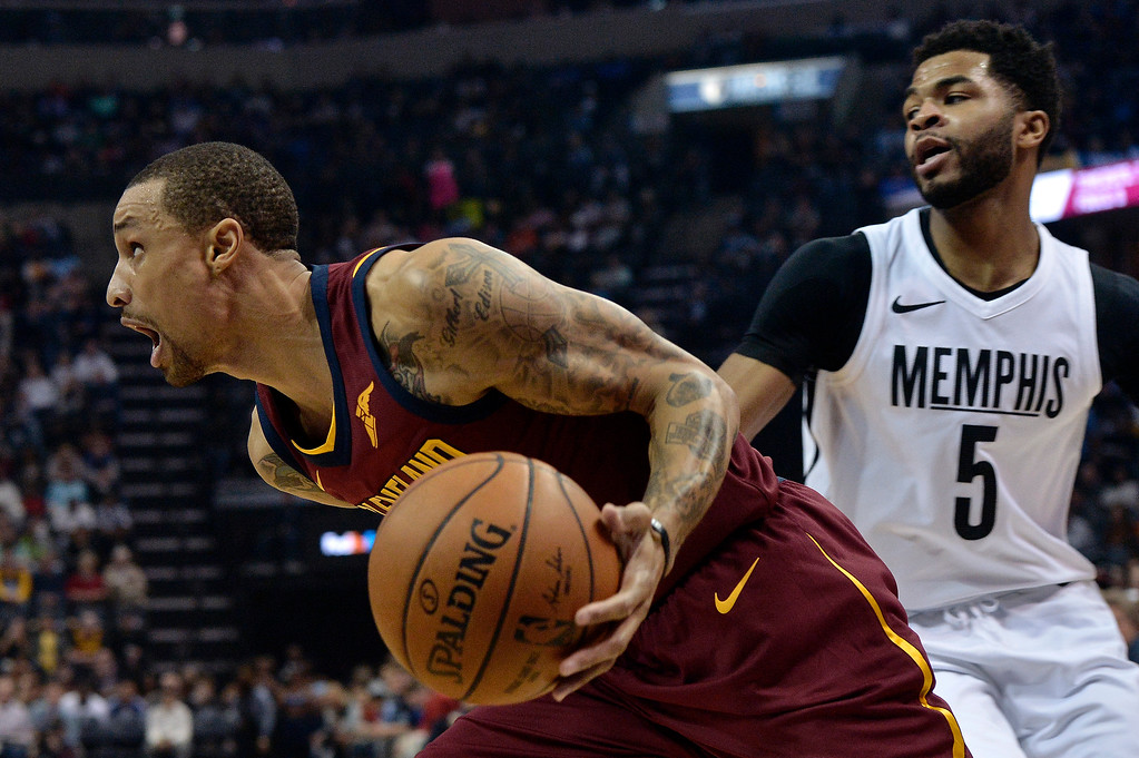 . Cleveland Cavaliers guard George Hill, left, drives against Memphis Grizzlies guard Andrew Harrison during the first half of an NBA basketball game Friday, Feb. 23, 2018, in Memphis, Tenn. (AP Photo/Brandon Dill)
