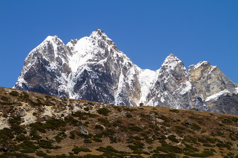 A chorten is dwarfed by the high Himalayan peaks behind it.