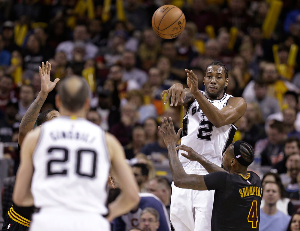 . San Antonio Spurs\' Kawhi Leonard (2) passes to Manu Ginobili (20) under pressure from Cleveland Cavaliers\' Iman Shumpert (4) during the second half of an NBA basketball game, Saturday, Jan. 21, 2017, in Cleveland. The Spurs won 118-115 in overtime. (AP Photo/Tony Dejak)