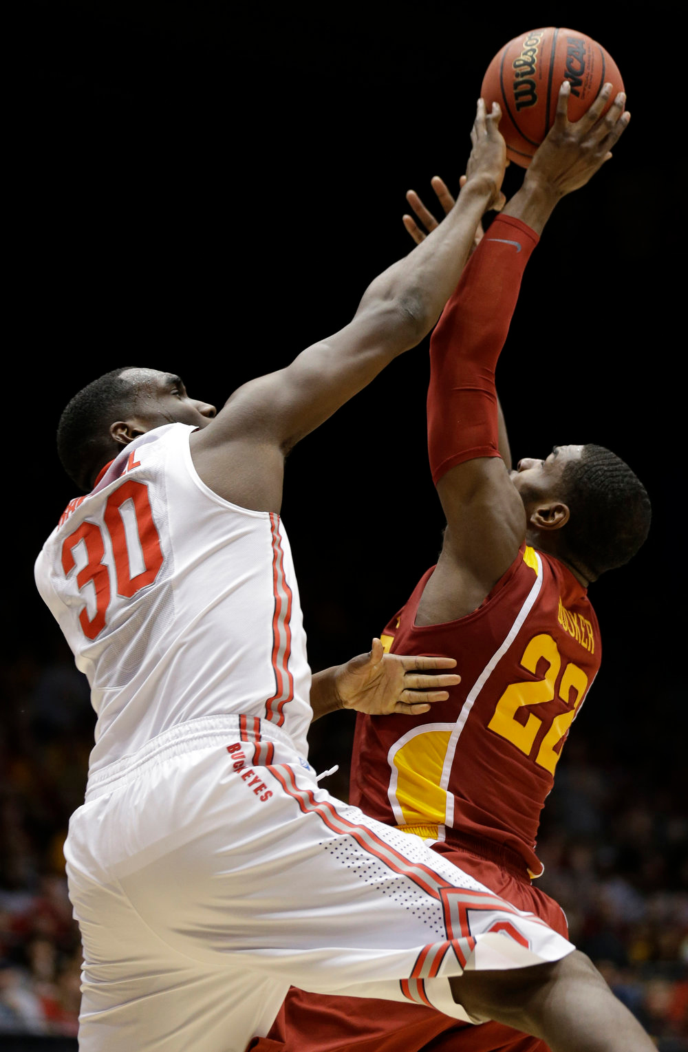 . Iowa State forward Anthony Booker (22) and Ohio State forward Evan Ravenel (30) go for a rebound in the first half of a third-round game of the NCAA college basketball tournament Sunday  March 24, 2013, in Dayton, Ohio. (AP Photo/Al Behrman)