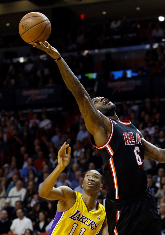 . Miami Heat forward LeBron James (6) goes to the basket as Los Angeles Lakers forward Wesley Johnson (11) looks on  during the second quarter of an NBA basketball game in Miami, Thursday, Jan. 23, 2014. (AP Photo/Alan Diaz)