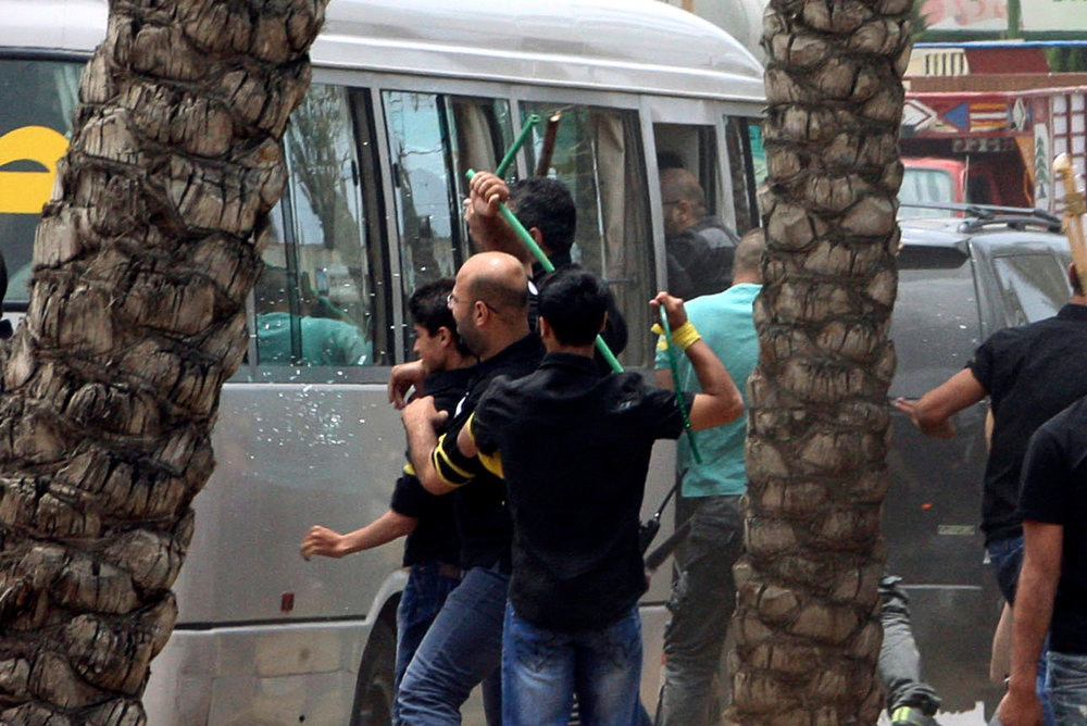 . Hezbollah supporters attack a bus carrying anti-Hezbollah protesters in front of the Iranian embassy in Beirut June 9, 2013. An unarmed Lebanese protester, a member of a small crowd demonstrating against the backing of Iran and its Hezbollah ally for Syrian President Bashar al-Assad, was killed on Sunday by gunfire in front of the embassy in Beirut, Lebanese security officials said.   REUTERS/ Stringer