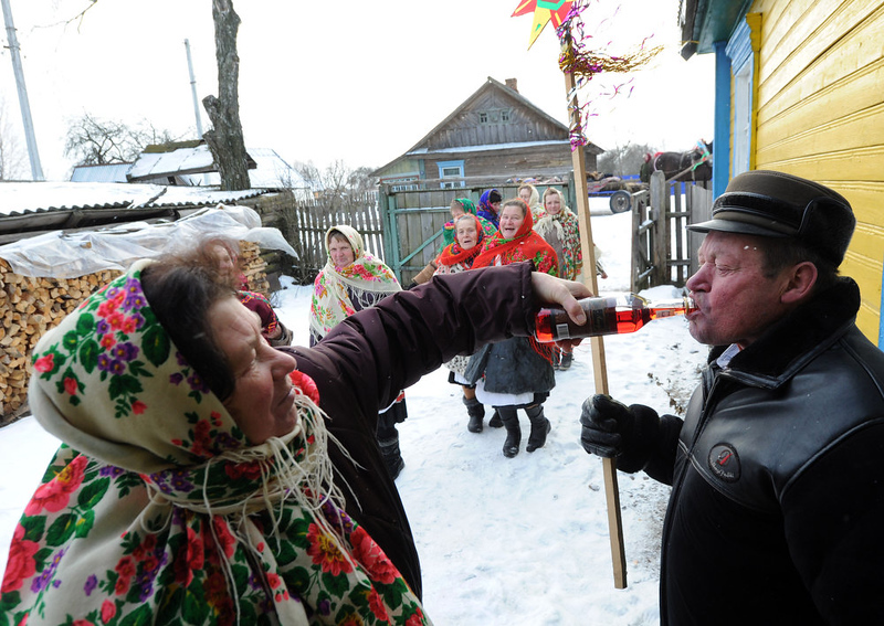 . A woman gives a drink to a person as they attend Christmas celebration in the town of Richev, some 290 km south from Minsk. on January 7, 2013. Orthodox Christians celebrate Christmas on January 7 in the Middle East, Russia and other Orthodox churches that use the old Julian calendar instead of the 17th-century Gregorian calendar adopted by Catholics, Protestants, Greek Orthodox and commonly used  in secular life around the world.   AFP PHOTO / VIKTOR DRACHEVVIKTOR DRACHEV/AFP/Getty Images