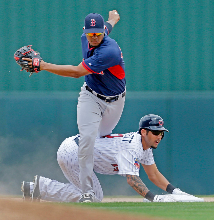 . Minnesota\'s Jason Bartlett is forced at second but breaks up a double play ball off the bat of first baseman Joe Mauer, as Red Sox shortstop Xander Bogaerts trips over him with the ball in the first inning. (AP Photo/Gerald Herbert)