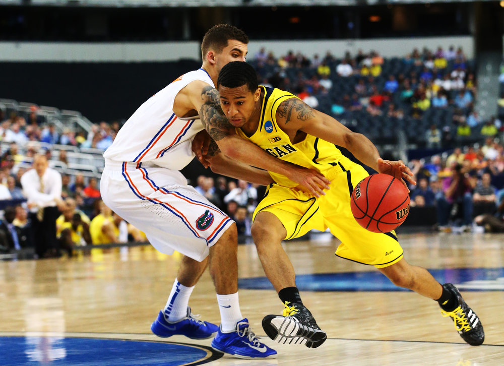Description of . Trey Burke #3 of the Michigan Wolverines drives against Scottie Wilbekin #5 of the Florida Gators in the first half during the South Regional Round Final of the 2013 NCAA Men\'s Basketball Tournament at Dallas Cowboys Stadium on March 31, 2013 in Arlington, Texas.  (Photo by Ronald Martinez/Getty Images)