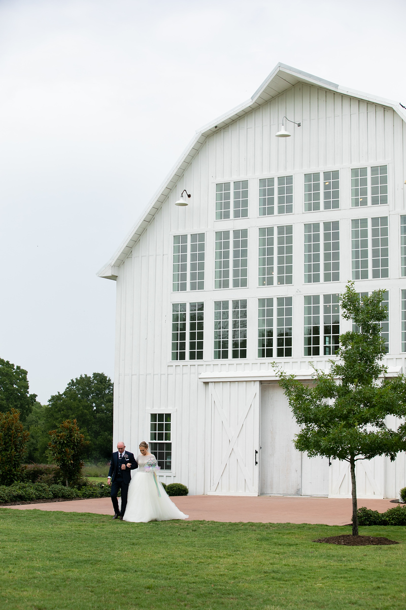 a bride and her father walking out of a large white barn before walking down the aisle