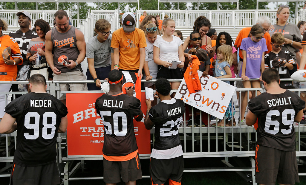. Cleveland Browns defensive end Jamie Meder (98), linebacker B.J. Bello (50) cornerback Joe Haden (23) and defensive end Karter Schult (69) sign autographs for fans after practice at the NFL football team\'s training camp facility, Thursday, July 27, 2017, in Berea, Ohio. (AP Photo/Tony Dejak)