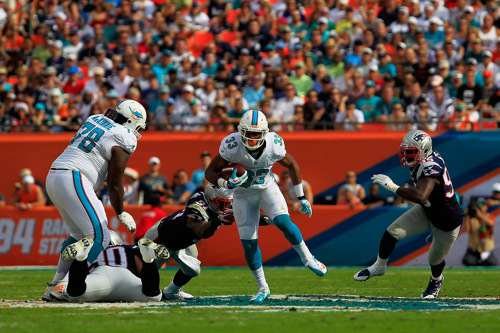 . Daniel Thomas #33 of the Miami Dolphins rushes the ball under pressure from  Jamie Collins #91 of the New England Patriots at Sun Life Stadium on December 15, 2013 in Miami Gardens, Florida.  (Photo by Chris Trotman/Getty Images)