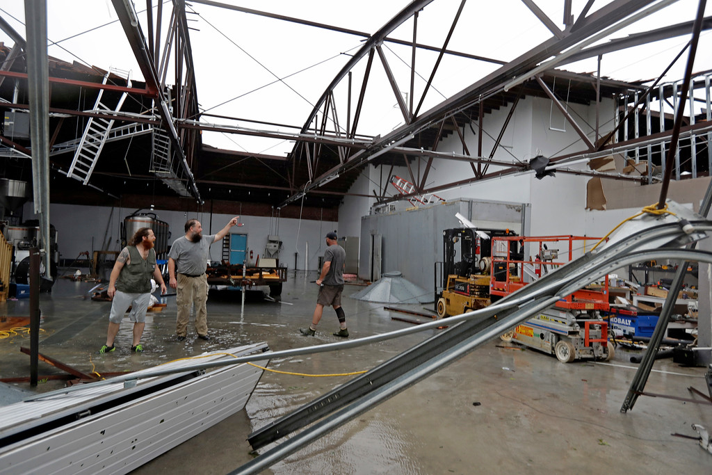 . Ethan Hall, right, Michael Jenkins, center, and Nash Fralick, left, examine damage to Tidewater Brewing Co. in Wilmington, N.C., after Hurricane Florence made landfall Friday, Sept. 14, 2018. (AP Photo/Chuck Burton)