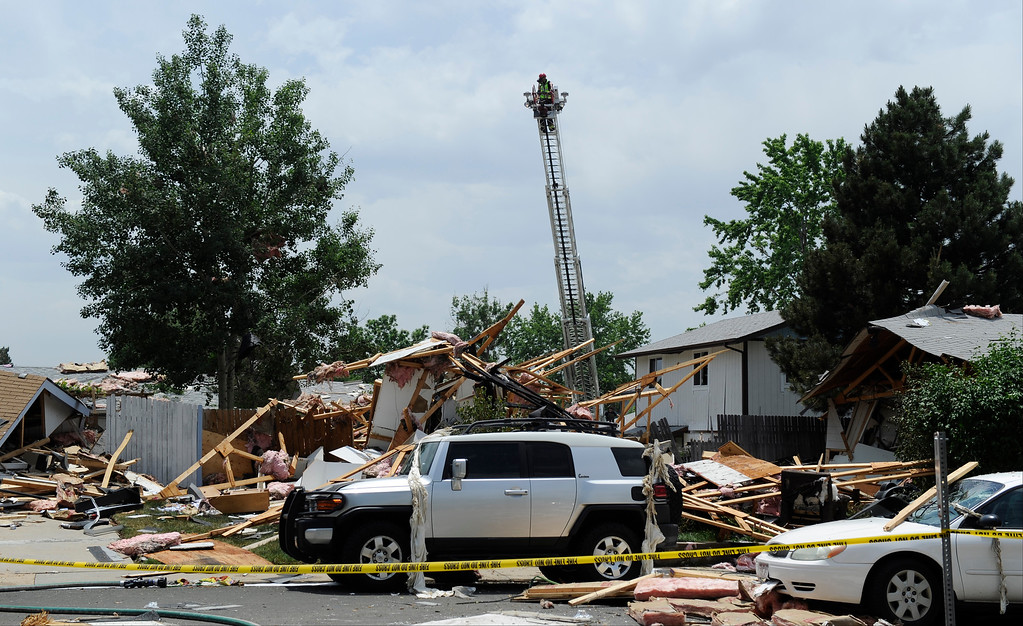 . A member of the North Area Tech Rescue Team gets a birds-eye view of a house explosion on the 9300 block of Ingalls Street in Westminster, Colorado.  (Photo By Andy Cross/The Denver Post)