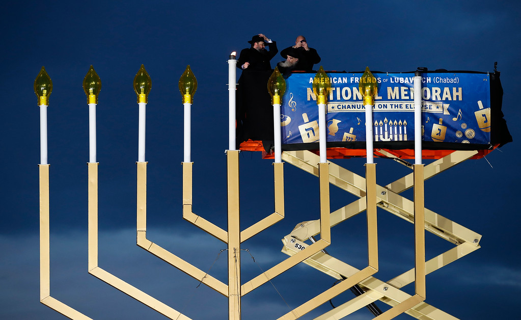 . From left, Rabbi Levi Shemtov, Rabbi Abraham Shemtov and National Economic Director Gary Cohn, struggle in the wind holding on to their hats, as they light the Menorah during the annual National Menorah Lighting, in celebration of Hanukkah, on the Ellipse near the White House in Washington, Tuesday, Dec. 12, 2017. (AP Photo/Carolyn Kaster)
