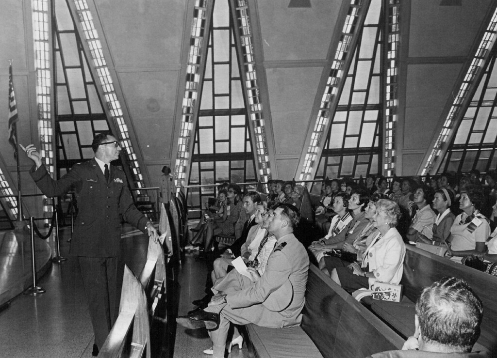 . Governors\' Wives learn About Architecture of chapel at united states air force Academy Detailing symbolism of structure is Maj. Gilbert Amelio, the academy\'s director of protocol. The three women in the front row, from left, are Mrs. Thomas Moorman, wife of the academy superintendent; Mrs. John Love, Colorado\'s first lady and Mrs. Spiro Agnew, wife of the vice president. The two men are presidential aides. 1969. The Denver Post Library Archive