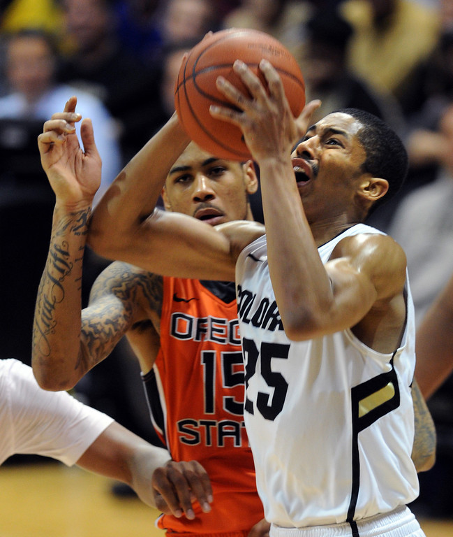 . Spencer Dinwiddie grimaces  as he drives past Eric Moreland of Oregon State during the second half of the March 9, 2013 game in Boulder.    (Cliff Grassmick/Boulder Daily Camera)