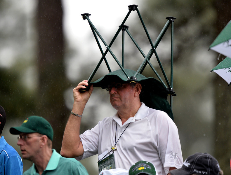 . A golf fan takes cover in the rain during the second round of the 77th Masters golf tournament at Augusta National Golf Club on April 12, 2013 in Augusta, Georgia.   JEWEL SAMAD/AFP/Getty Images