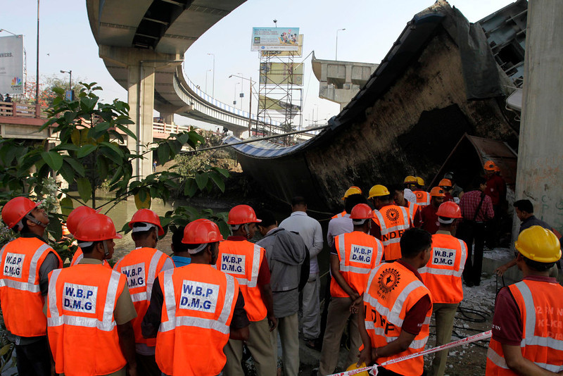 . Rescue workers of the Disaster Management Group gather at the site where a section of a bridge collapsed early morning in Kolkata, India, Sunday, March 3, 2013. Three persons traveling in a truck that was passing through the bridge were seriously injured in the accident. (AP Photo/Bikas Das)